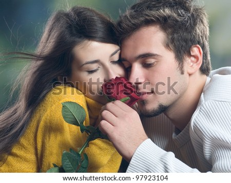 Young happy amorous couple with rose, outdoors - stock photo