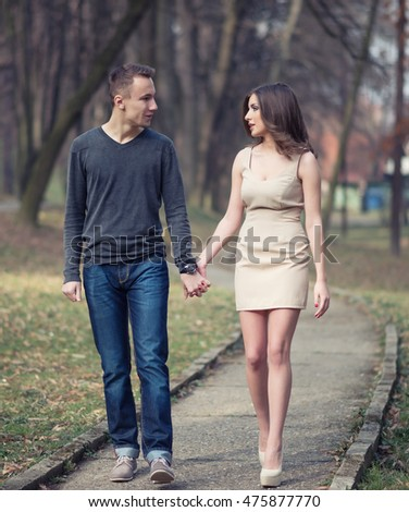 Young, happy and attractive couple enjoying together in walk through the city park. Urban outdoors.