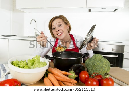 young happy and attractive home cook woman in red apron at domestic kitchen holding saucepan tasting hot soup vegetable stew smelling delicious in lifestyle and amateur cooking success - stock photo
