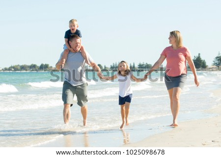 young happy and beautiful family mother father holding hand of son and daughter walking joyful on the beach enjoying Summer holidays in parents and siblings lifestyle concept