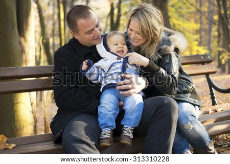 Young happy and cheerful family enjoying outdoors in a beautiful autumn day. Autumn foliage. Father, mother and their little son are sitting on a park bench and smiling. - stock photo