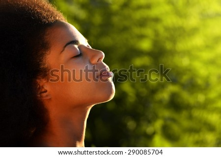 young happy and  pretty curly afro woman closeup portrait on natural background - stock photo