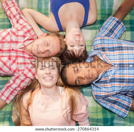 Young happy and smiling company lay on mat and posing for camera - stock photo