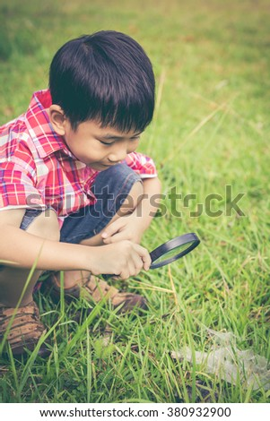 Young happy asian boy enjoying and exploring nature at water droplets on a spider web (cobweb) with magnifying glass. Outdoors in the day time with bright sunlight. Retro style. - stock photo