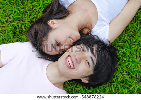 Young happy asian couple laying on grass