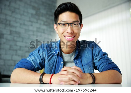 Young happy asian man sitting at the table - stock photo