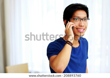 Young happy Asian man talking on the phone - stock photo