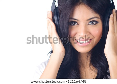 Young happy asian woman listening to music on white isolated - stock photo