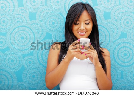 Young happy asian woman with smartphone standing against blue background - stock photo