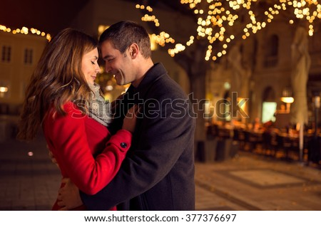Young happy attractive amorous couple embracing  and kissing outdoor