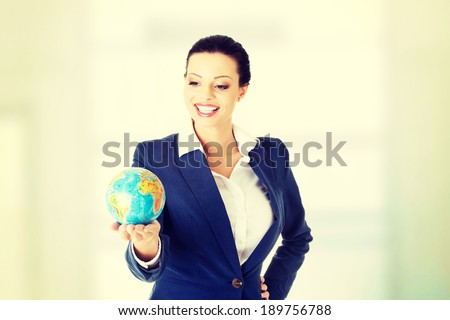 Young happy attractive brunette businesswoman holding the globe
