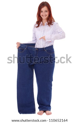 Young happy attractive female in huge old pair of jeans, diet concept, isolated on white - stock photo
