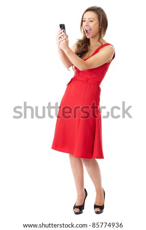 Young happy attractive female in red dress takes photos using her mobile phone, shoot over white background - stock photo