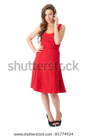 Young happy attractive female in red dress text over mobile phone, shoot over white background