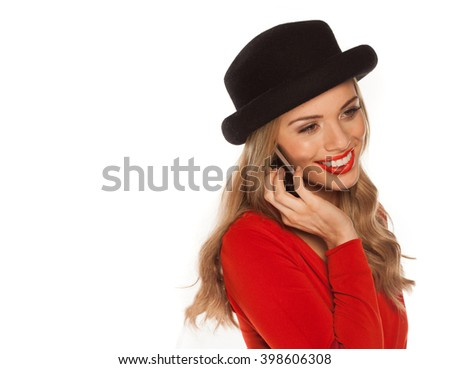 Young happy attractive female in red dress using her mobile phone, shoot over white background