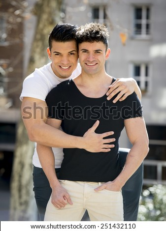 young happy attractive gay men couple with strong fit body cuddling posing outdoors on street in sexual freedom and free homosexual love concept in urban background - stock photo