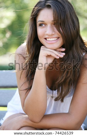 Young happy attractive girl enjoys summer day at the park.