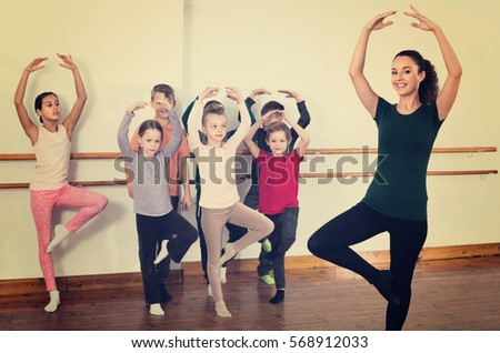 Young happy  ballet dancers exercising in ballroom