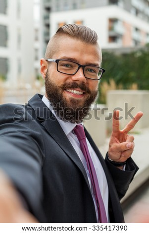 Young happy bearded businessman standing outside office building and taking selfie. Outdoor photo - stock photo