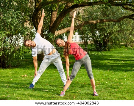 Young happy beautiful couple practicing stretching outdoors. Full-length.