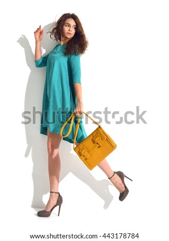 Young happy beautiful curly brunette woman posing in blue mint fashion body dress cloth with brown hand bag clutch on a white background