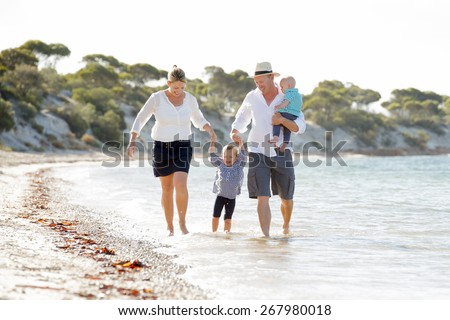 young happy beautiful family walking on sand together at beach sea shore enjoying summer holidays , father with baby boy, mother and cute little daughter playing in vacation lifestyle concept - stock photo