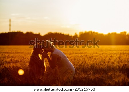 Young happy beautiful mother and her daughter . Happy family jumping together in a circle having fun and expressing emotions of joy, freedom, success. Silhouettes on sunny sky - stock photo
