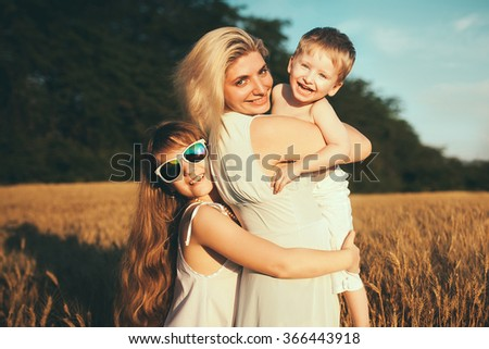 Young happy beautiful mother,son and her daughter . Happy family jumping together in a circle having fun and expressing emotions of joy, freedom, success.  - stock photo