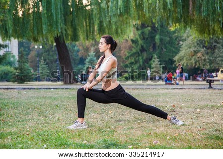 Young happy beautiful sexy girl is stretching in the park garden. people background. with dark hair and black and white sport suit and happiness and smile. on summer or autumn time season.