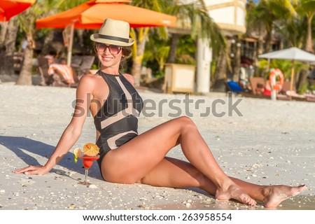 young happy beautiful woman enjoying summer vacation on tropical sand beach, sunbathing, outdoor portrait - stock photo
