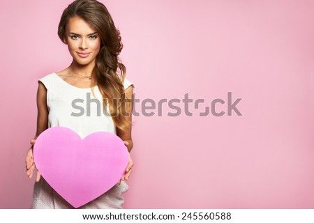 Young happy beautiful woman hold Love symbol red heart. Isolated on studio pink background female model - stock photo