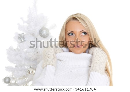 Young happy beautiful  woman in winter clothes stands near Christmas tree on a white background. - stock photo