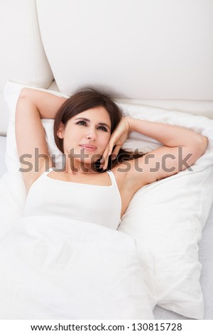 Young Happy Beautiful Woman Lying On Bed - stock photo