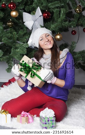 Young happy beautiful woman near new year tree with present - stock photo