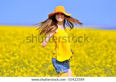 young happy beautiful  woman on blooming rapeseed field in summer - stock photo