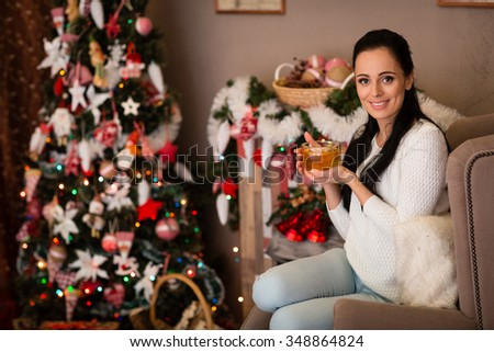 Young happy beautiful woman with cup of tea sits near Christmas tree in the room of the house. Merry Christmas and New Year. - stock photo