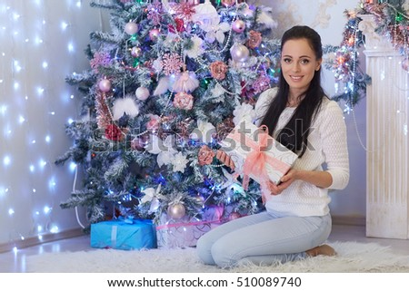 Young happy beautiful woman with gift box sits near Christmas tree in the room of the house. Merry Christmas and New Year.