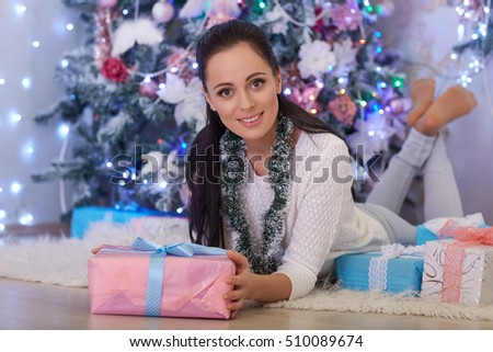Young happy beautiful woman with gift boxes lies near Christmas tree in the room of the house. Merry Christmas and New Year.