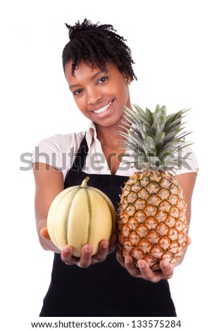 Young happy black / african american woman selling fresh fruits isolated on white background - stock photo