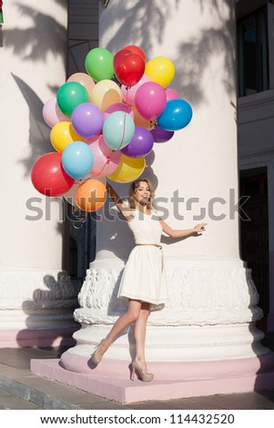 Young happy blond woman with colorful latex balloons keeping her dress, urban scene, outdoors - stock photo