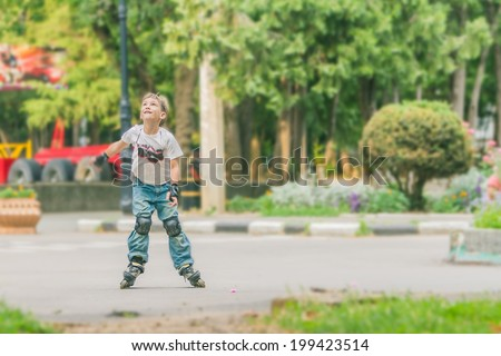 young happy boy having fun on roller skates on natural background - stock photo