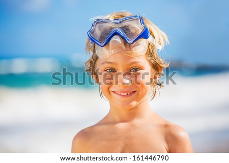 Young happy boy having fun on tropical beach, wearing snorkel mask - stock photo