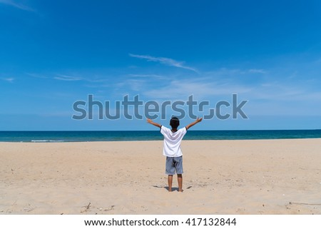 Young happy boy relaxing on the tropical beach with open arms in daylight.
