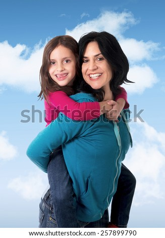 young happy Brazilian mother carrying on her back  little daughter having fun together smiling posing on a blue sky with clouds in parenthood and family love concept - stock photo