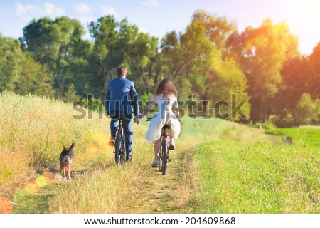 Young happy bride and groom ride bicycles in the meadow back to camera and holding hands. - stock photo