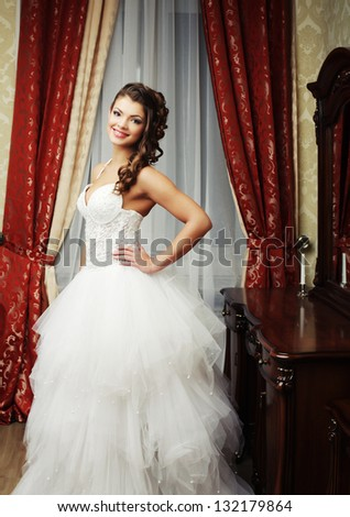 young happy bride posing in hotel room