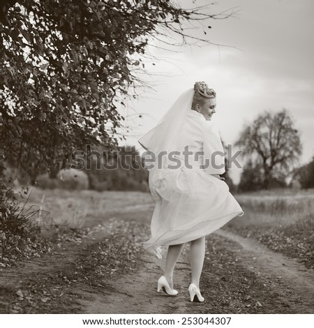 Young happy bride posing on countryside road.