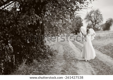 Young happy bride posing on countryside road.  - stock photo