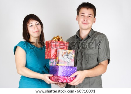 young happy brunette man and girl holding many gifts and smiling