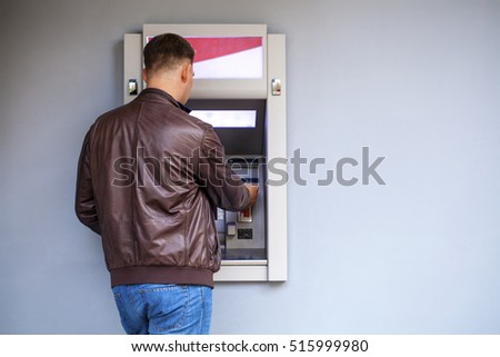 Young happy brunette man withdrawing money from credit card at ATM